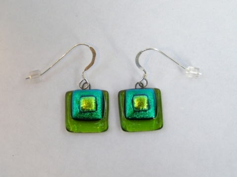 Paula Woodward - These earrings are made from three layers of fused glass. A transparent green base with layers of emerald and light green dichroic glass on top.  They are lightweight to wear, are finished with sterling silver earwires, and match the Spring Green Layered Pendant. £16
