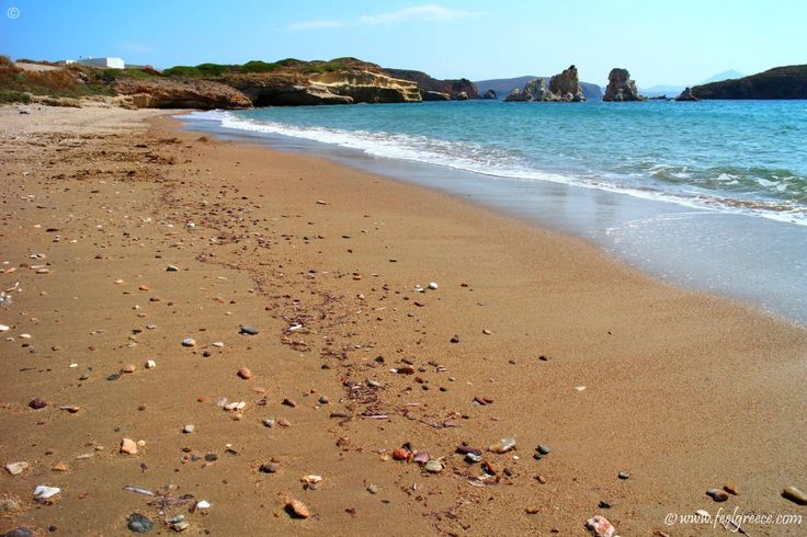 The sandy Mavrospilia beach with caves in the rocks. Small pebbles here and there.