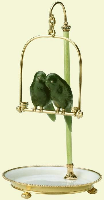 A pair of budgerigars on a perch, by Fabergé. The birds carved in nephrite with rose diamond eyes, the perch of silver-gilt with green and white guilloché enamel and rose diamonds. Mark of Michael Perchin, 1903. Probably acquired by King Edward VII and Queen Alexandra.