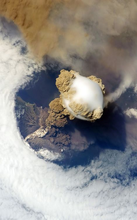 Pileus clouds (small clouds formed on top of the big ones) above the Sarychev volcano as it erupts, at the Kuril Islands, Russia.