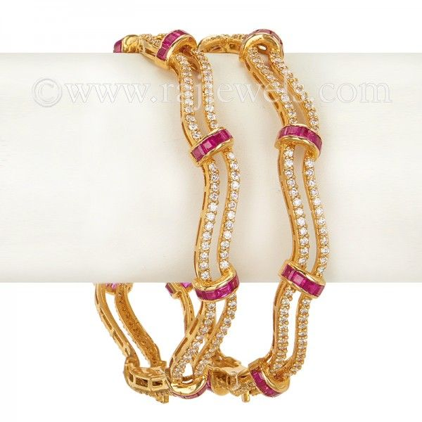 Fancy wavy design #diamond #bangles in 18 karat yellow #gold, studded with accents of #ruby gemstones, available in set of two, featuring 6.48 carats weight of diamonds. IGI Certificate is available with the purchase. - See more at: https://www.rajjewels.com/18-k-gold-wavy-diamond-ruby-bangle-set.html#sthash.NRU0SawM.dpuf