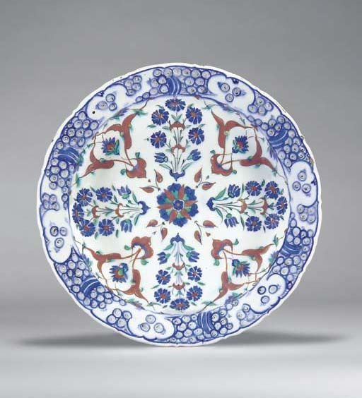 AN IZNIK POTTERY DISH OTTOMAN TURKEY, CIRCA 1580 With sloping slightly cusped rim on short foot, the white interior with alternating blue peony sprays and red split-leaves enclosing blue palmettes, radiating around central blue and green rosette with red petals, the rim with stylized blue wave and rock motif, the exterior with alternating paired tulip and flowerhead, 13¾in. (35.2cm.) diam.