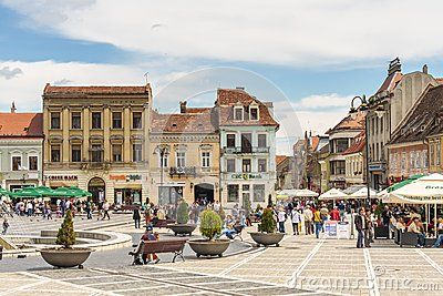 View of the Council Square (Piata Sfatului) with many tourists enjoying a walk, relaxing and sightseeing in Brasov city, Romania.