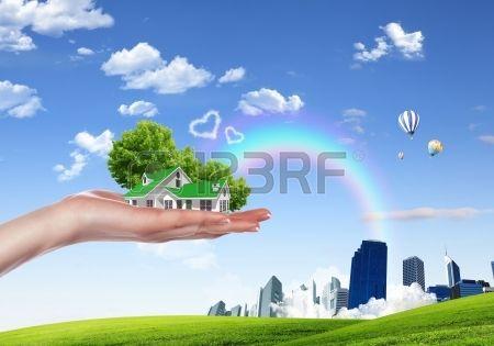 Menschliche Hand die H user von Natur aus gegen den blauen Himmel und Regenbogen umgeben Lizenzfreie Bilder
