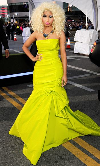 AMA 2012: Nicki Minaj  The most-nominated artist of the evening walked the red carpet in a body-contouring neon yellow Monique Lhuillier gown, paired with a voluminous blonde primped bob, her signature hot pink lips, and a Charles Albert ring and necklace.