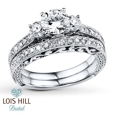 Classic elements meet the unique style of designer Lois Hill in this awe-inspiring bridal set for her from Lois Hill Bridal. A trio of round diamonds crowns the engagement ring, while more round diamonds and milgrain flow along the band of the engagement ring and the matching wedding band. The signature graceful scroll motif elevates the sides of the rings, which are crafted in 14K white gold. The amazing bridal set sparkles with a total diamond weight of 1 7/8 carats. Diamond Total Carat…