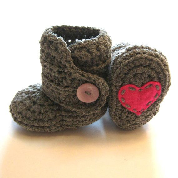 Crochet baby booties with a bright pink heart on the bottom. <3