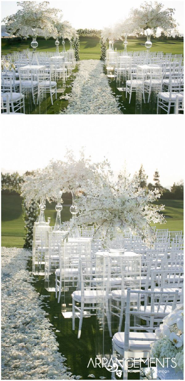 Love white weddings!   Large orchid arrangements on lucite pillars with a runner of petals down the aisle.   Decor | Arrangements Floral & Party Design (www.arrangementsdesign.com) Coordinator | Celebrations of joy (neveradryeye.wordpress.com)  Cake | Exquisite Desserts (www.exquisitedesserts.net)
