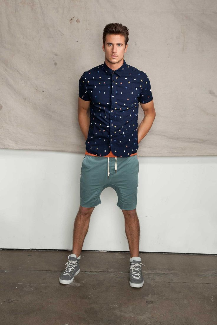 Shop this look on Lookastic:  http://lookastic.com/men/looks/navy-short-sleeve-shirt-orange-crew-neck-t-shirt-teal-shorts-grey-high-top-sneakers/10409  — Navy Print Short Sleeve Shirt  — Orange Crew-neck T-shirt  — Teal Shorts  — Grey High Top Sneakers