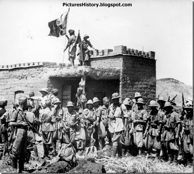 Triumphant Italians pose against a captured British fortification during the campaign in North Africa