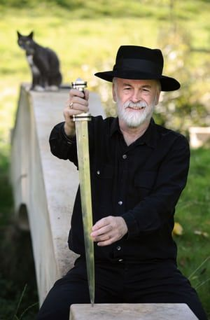 Terry Pratchett at home in Wiltshire with the sword that he forged from his own iron ore