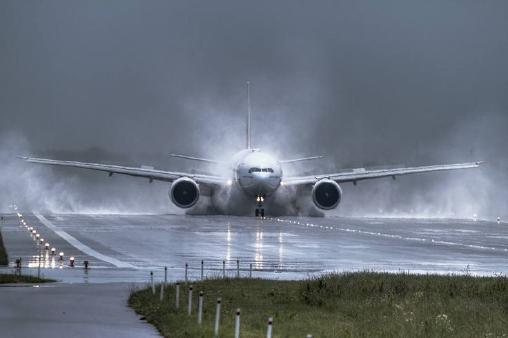 A Boeing 777-300ER lands at the Warsaw Chopin Airport during a strong storm