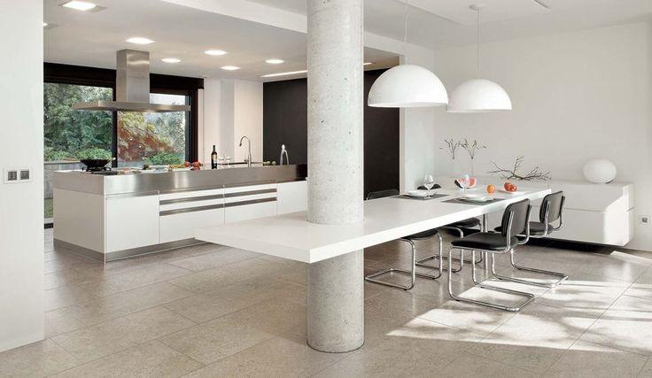 Moderne keuken met eiland en lichte tinten en één zwarte muur.