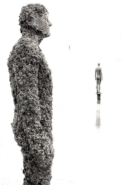 """Another Place"" Anthony Gormley statues on Crosby beach, encrusted with barnacles"