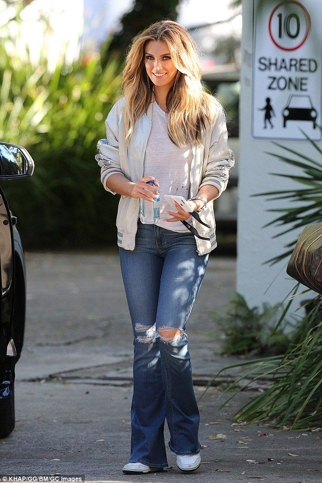 'Hearts are wild creatures, that's why our ribs are in cages': Delta Goodrem, 31, showed off inspirational motto on her phone as she stepped out in flared jeans on Tuesday