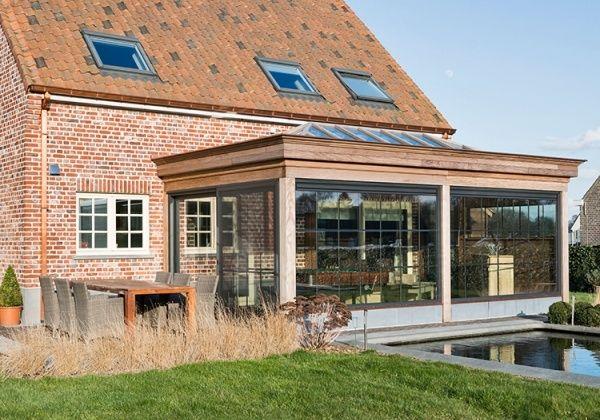 Deze veranda met plat dak is er gekomen om winter en zomer volop te genieten van de mooie landelijke tuin en haar natuurlijk licht. De veranda werd naadloos aan de bestaande woning geïntegreerd.