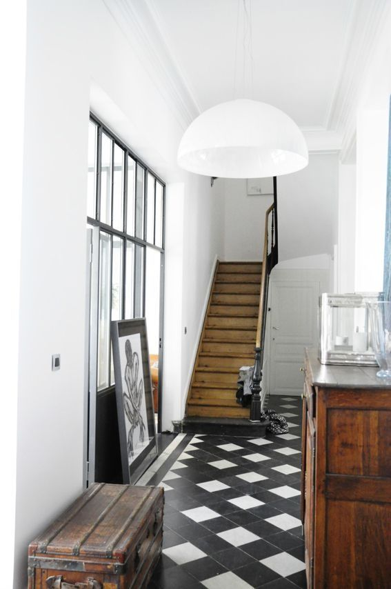 Patterned tile, lovely wood stairway, & window / Une entrée avec un sol en noir et blanc
