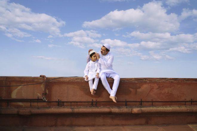 """Por fim, numa mesquita em Nova Déli, na Índia, pai e filho estão juntos na celebração muçulmana que marca o fim do jejum do Ramadã. """"A fotografia mostra o bonito laço que essas duas gerações construíram de maneira simples e amável"""", afirmou o fotógrafo Jobit George."""