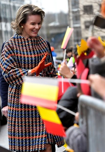 Queen Mathilde of Belgium who was spotted on a busy day of engagements wearing a Natan checked belted coat and she added even more color to the look with a pair of bright orange leather gloves as she greeted well-wishers in Vilvoorde