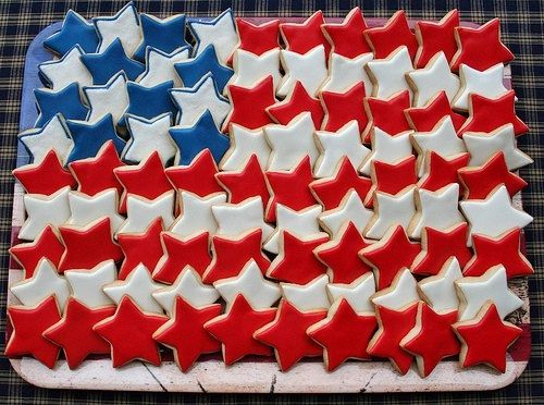4th of July Party Food Ideas! Red, White, and Blue Star Sugar Cookies arranged on a plate to resemble the American Flag. You can top with Sprinkles to match each cookie for a more glittery look.