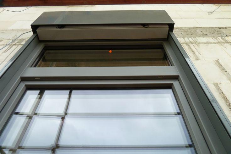 Die Fenster werden aus Kunststoff innen Weiß, außen Basaltgrau. Die Kästen der Raffstore werden auch Basaltgrau, genau wie die Schienen. Die Fensterbänke und die Lamellen werden dann in Alu eloxiert.