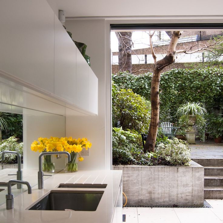 William Tozer Associates has overhauled a Victorian terraced house in north London, introducing a white, modern living area that faces out onto a neighbouring brutalist estate.
