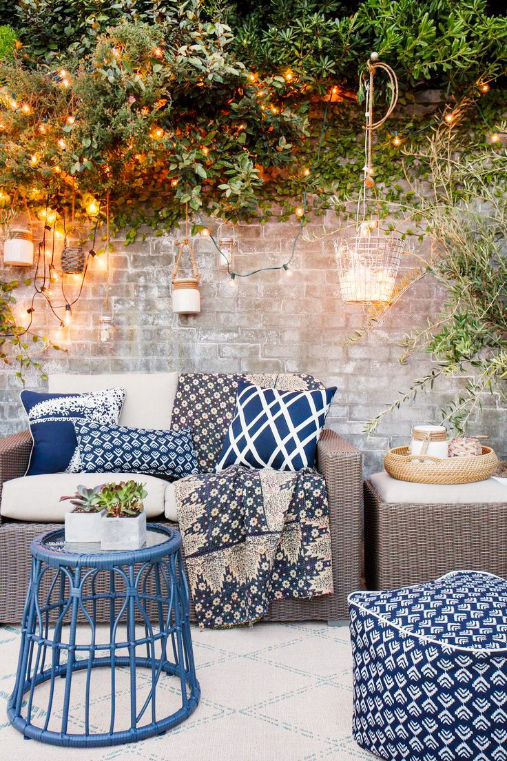 Stone outdoor space with blue pillows, neutral sofa, and hanging lights