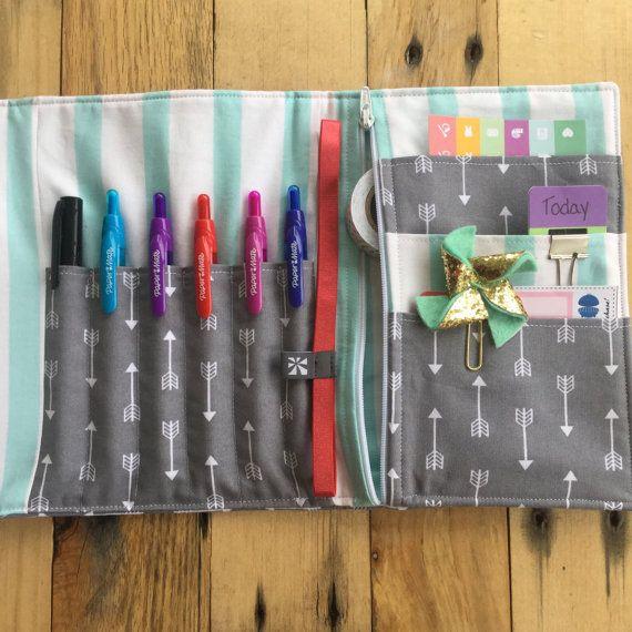 Pochette à crayon accessoire planificateur parfait pour le fanatique de planificateur !  ❤️ Recevez un cadeau gratuit avec chaque pochette accessoire planificateur acheter ! ❤️ Caractéristiques :  Fabriqué à partir de tissu de coton  Bordée dinterfaçage pour la longévité  6 emplacements de crayon/stylo  Poche zippée mesure 5,75 pouces x 8 pouces parfait pour ruban adhésif, etc..  3 poches idéal pour les autocollants, clips de charme, etc..  Fermeture bouton pression magnétique métal  Le…