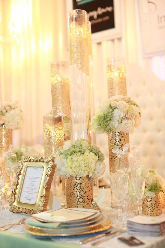 What a stunning look...this is very fit, tall glass cylinders gold leaf dollies...I would love to do this for a wedding....