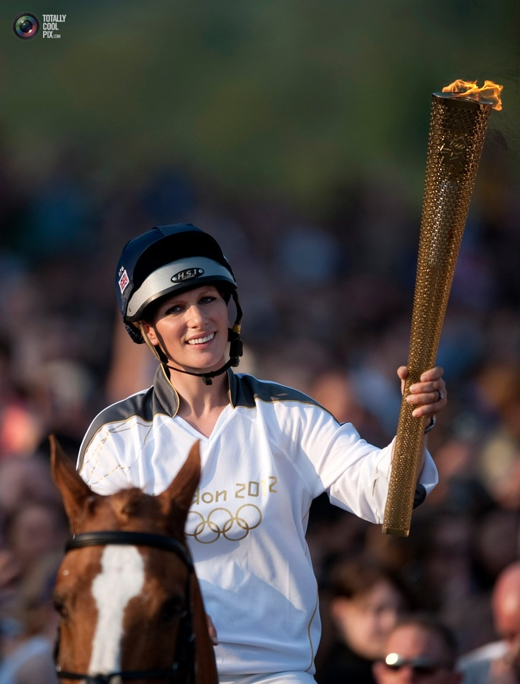 Zara Phillips holds the Olympic torch while riding through Cheltenham race course in Cheltenham. KIERAN DOHERTY/REUTERS