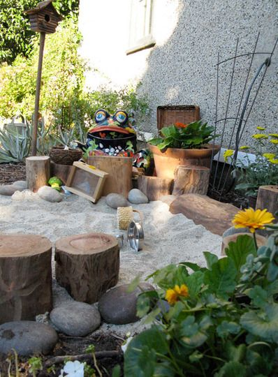 love the logs and the rocks and the flowers with the sand box...