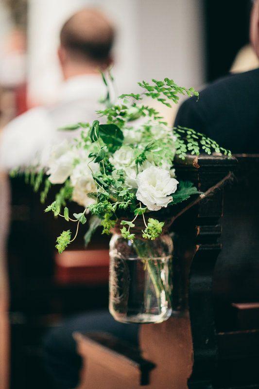 Pew marker of a mason jar filled with white hydrangea, white lisianthus , bupleurum and maiden hair fern.