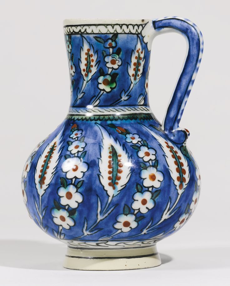 AN IZNIK POLYCHROME POTTERY JUG, TURKEY, CIRCA 1575 with pyriform body and slightly flaring neck on an everted foot with an S-shaped handle attached at the rim and shoulder, with an underglaze cobalt blue ground and a design consisting of two rows of alternating saz leaves and prunus wreaths with green and relief red details and black outlines 19.3cm. height.