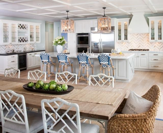 An open floor plan features a salvaged wood rectangular dining table lined with white faux bamboo chairs as well as seagrass dining chairs placed at each end of the table.