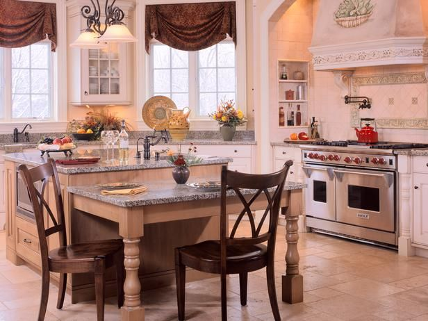 ❥ White-colored cabinetry mixed with stained maple lends a light, airy look to this traditional kitchen. An angled window wall work area draws natural light while a graceful arch and an artistic hood set the stage for everyday culinary drama. Design by Gail Drury.