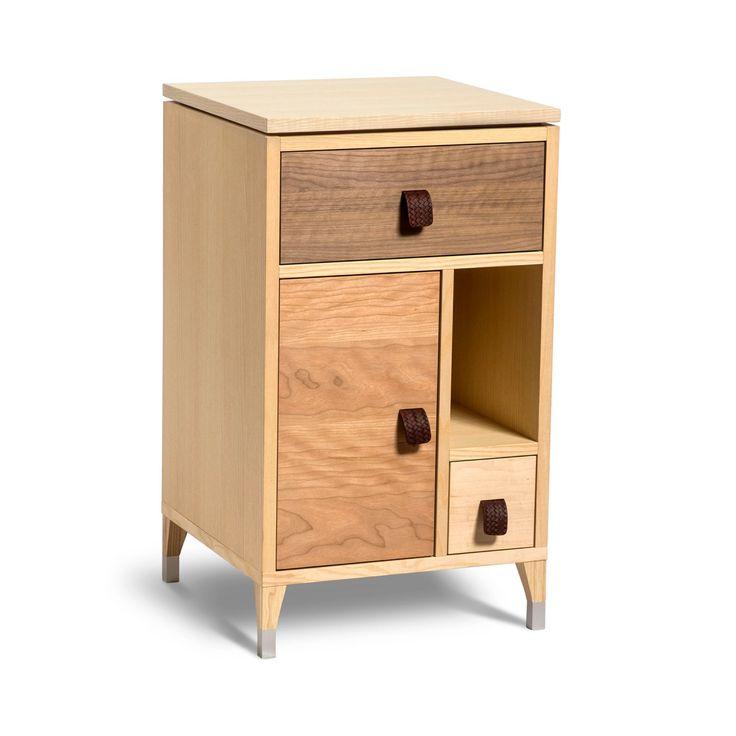 """Abisko sängbord med låga ben. Finns i """"flerfanér"""" eller i vitlack. Sängbordet finns även i en variant med högre ben. Utföranden:Vitlack eller blandade fan"""