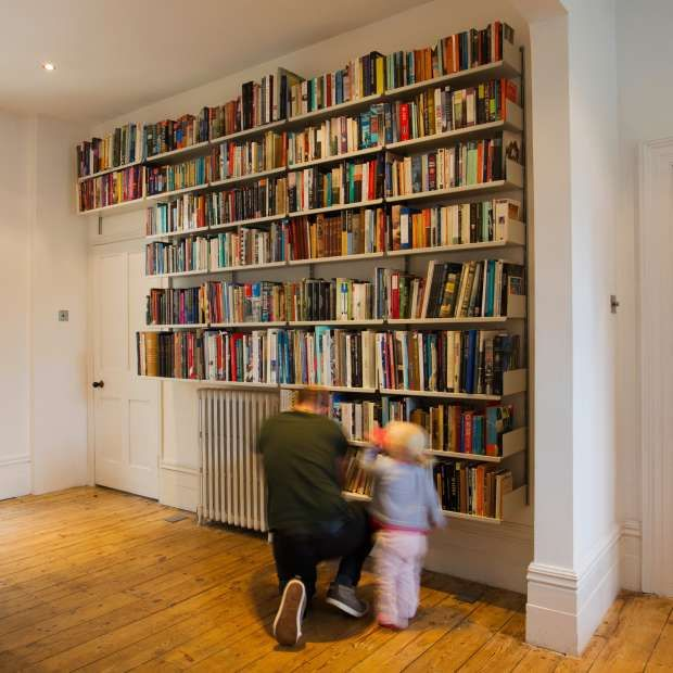 Wall-mounted shelves find their way around a radiator and door. Shelf depths of 22cm and 30cm accommodate the library