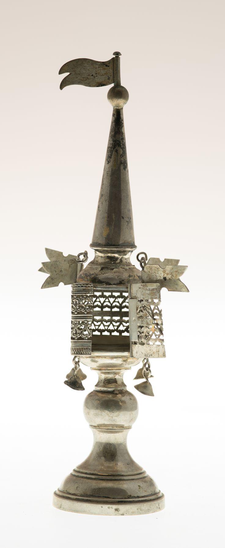 Stopa okrągła, profilowana, trzon tralkowy. Pojemnik czworoboczny, wykonany z taśmy ażurowanej, drzwiczki z fragmentu tej samej taśmy. W górnych narożnikach pojemniczka chorągiewki, w dolnych, odpowiednio, dzwoneczki. W zwieńczeniu iglica zakończona kulką i chorągiewką.  #Balsaminka #PMA #Muzeum #Museum #hadas #besamim #psumbyks #szmekier #judaica #polin