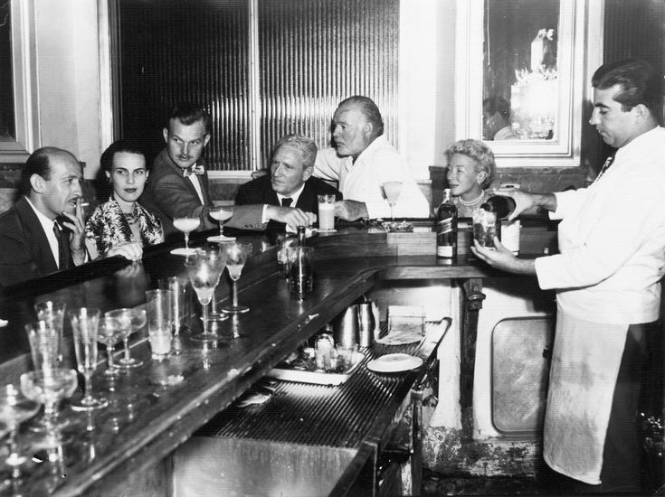 "EH05084P Spencer Tracy and Ernest Hemingway sitting with friends at the bar at La Florida (""Floridita""), Havana, Cuba, circa 1955."