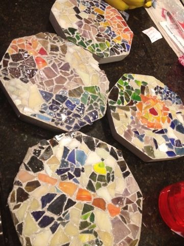Homemade stepping stones: using plastic trays as a base, and cement. Can use natural decorations instead of bright ones. Can fit together to create paving.