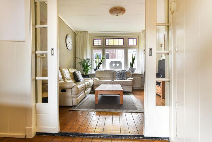 De woning heeft een sfeervolle woonkamer met diverse authentieke stijlelementen, zoals de glas in lood ramen, lambrisering aan de wanden en de en suite deuren.