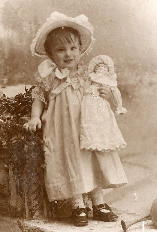 ADORABLE LITTLE GIRL, ABOUT 2, WITH HER DOLL IN ARMS,THERE'S ALSO A WATERING CAN NEXT TO HER, FROM ST. LOUIS, MO  circa late 1800's to early 1900's