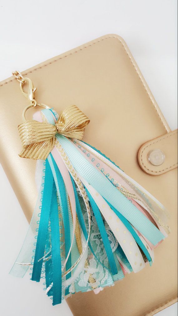 Gorgeous color combination of teal, ocean blue, peach, ivory and gold tassel. All our tassels are multi-functional and can be added to any existing accessories. Perfect for planners, handbags, pack backs, keys and so much more.  Handmade with lots of love using quality fibers to create this beautifully for you. Close attention to detail and quality made. This tassel measures 5 with just enough fluff, subtle but lovely. Attached to large gold metal split ring and large gold metal lobster…