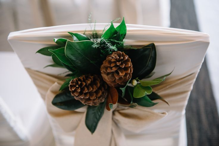 Wedding chairs marked with clusters of magnolia leaves and pine cones.  Flowers by Janie-Calgary Wedding Florist www.flowersbyjanie.com  Photo: http://abbyplusdave.com