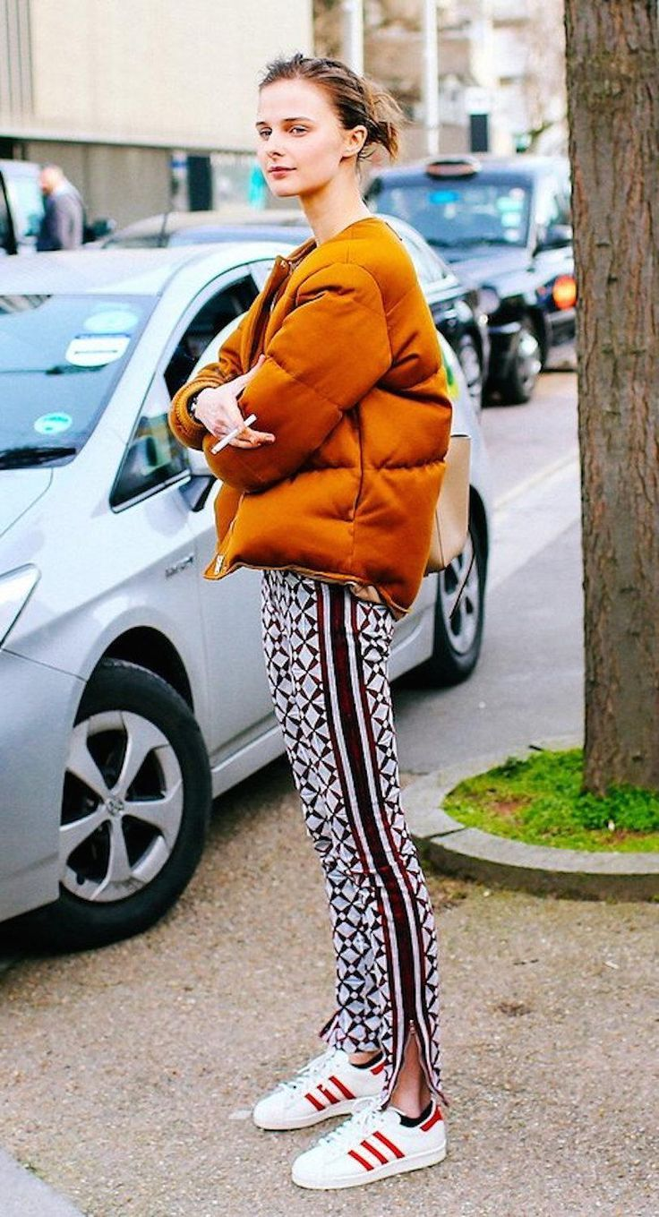 Orange puffer jacket, cotton printed pants and Adidas sneakers