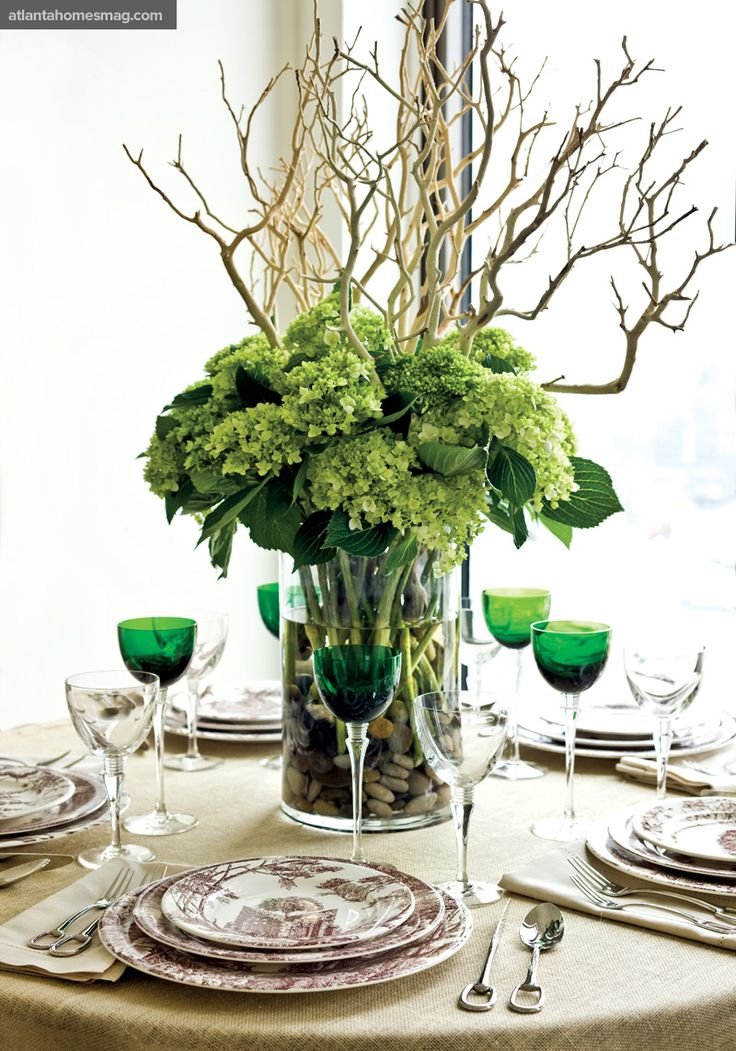 +/+ Pops of Color    Emerald-green Saint-Louis crystal glasses, Puiforcat silver flatware and Hermès china look dazzling alongside a sculptural floral arrangement composed of hydrangea and driftwood. All pieces available through Hermès of Paris in Buckhead.