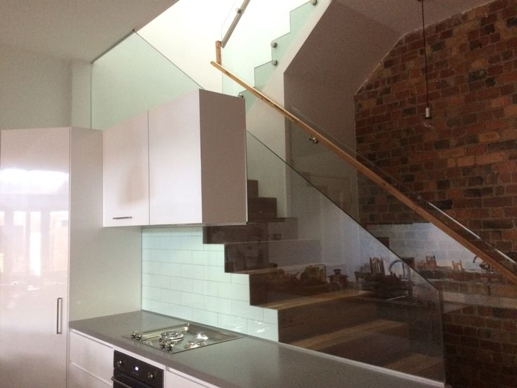 Glass splash back and balustrade. Exposed brick, spotted gum stair treads and Caesarstone bench top.
