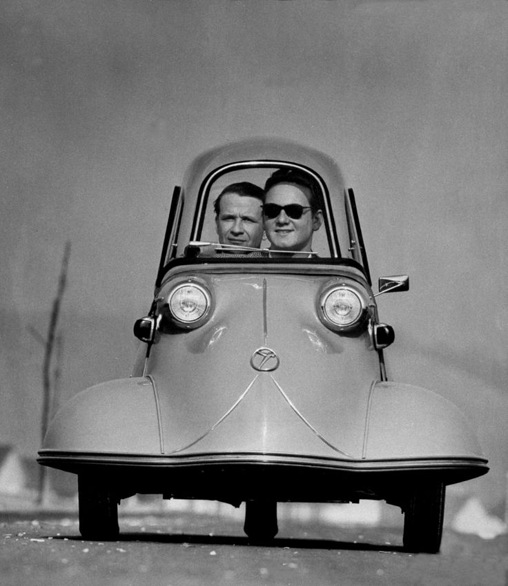 Front shot of two men riding in the three wheeled German made Messerschmidt, 1954