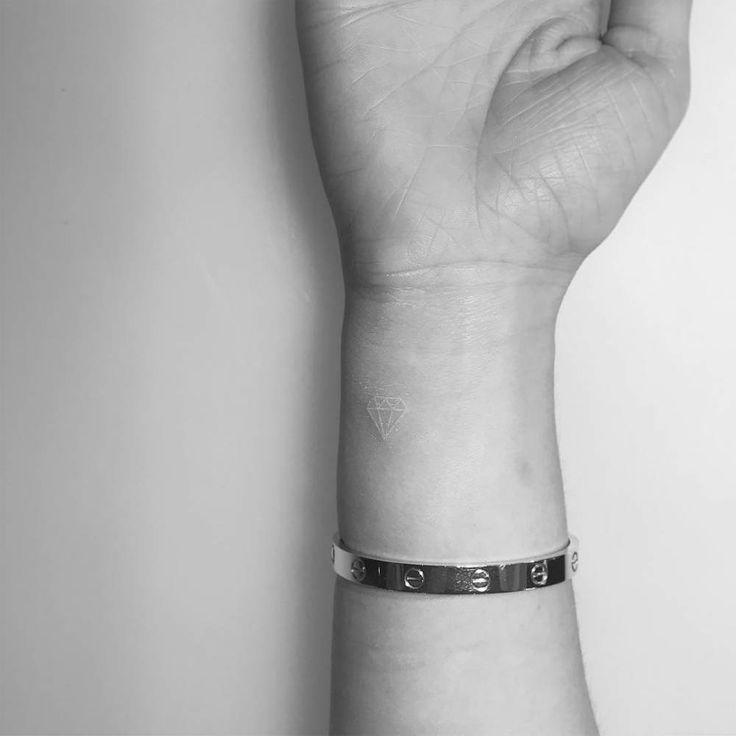 White ink diamond tattoo on the wrist.