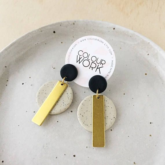 〰 The Brass Collection 〰 A lovely pair of circle statement earrings in a two tone colour palette with a brass rectangular bar. Jet Black & Speckled Sand. Details: Approx. 50mm length Approx. 28mm width Approx. 2-3 mm thickness Materials: - Surgical steel ear posts - Brass jump rings -